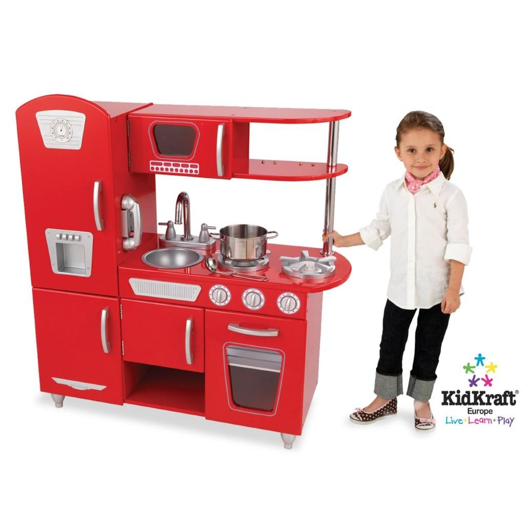 little girl standing next to red play kitchen