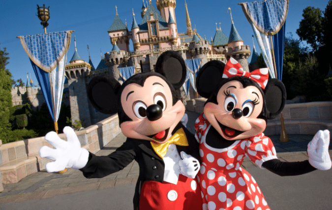 mickey and minnie mouse in front of castle