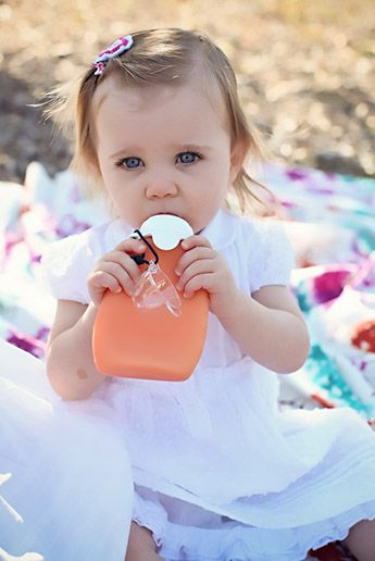 little girl drinking from a sili squeeze