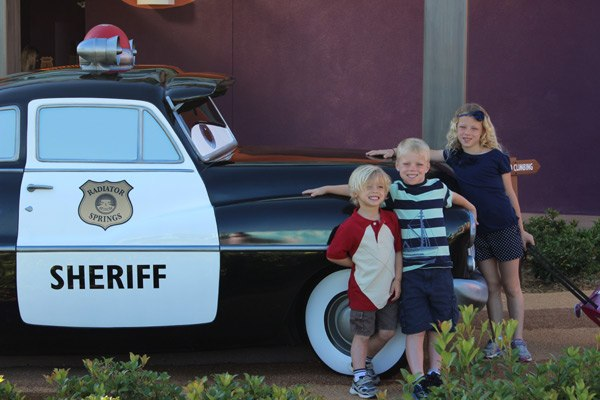three kids in front of sheriff car in disney