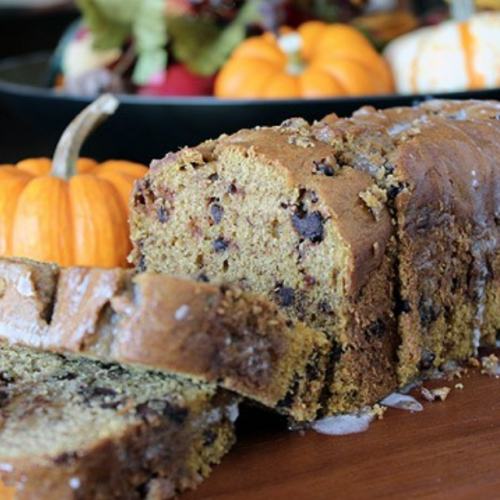 pumpkin bread with two slices cut on cutting board