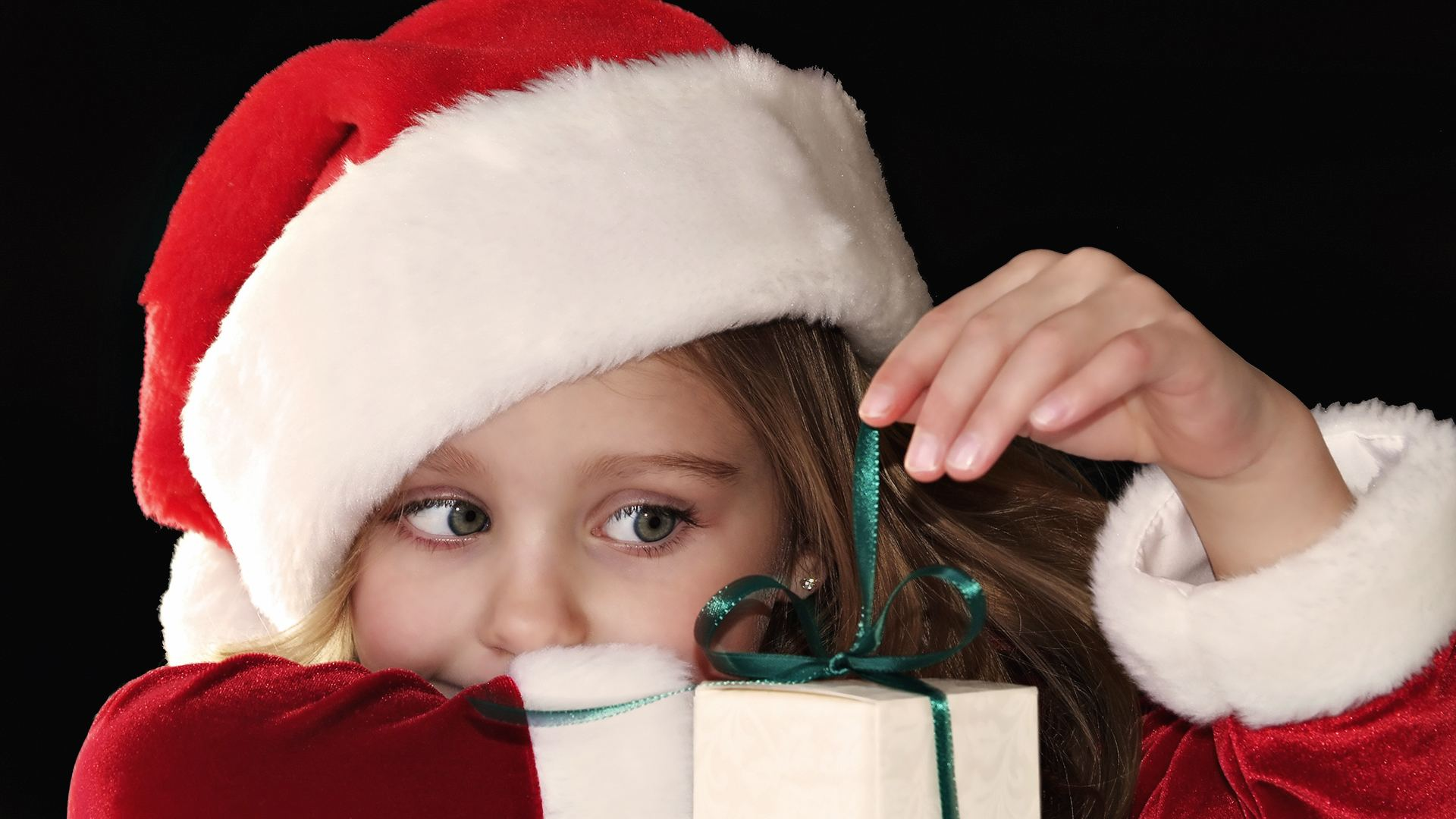 little girl with santa hat opening gift