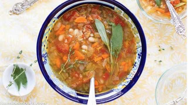 white bean soup in colorful bowl with spoon