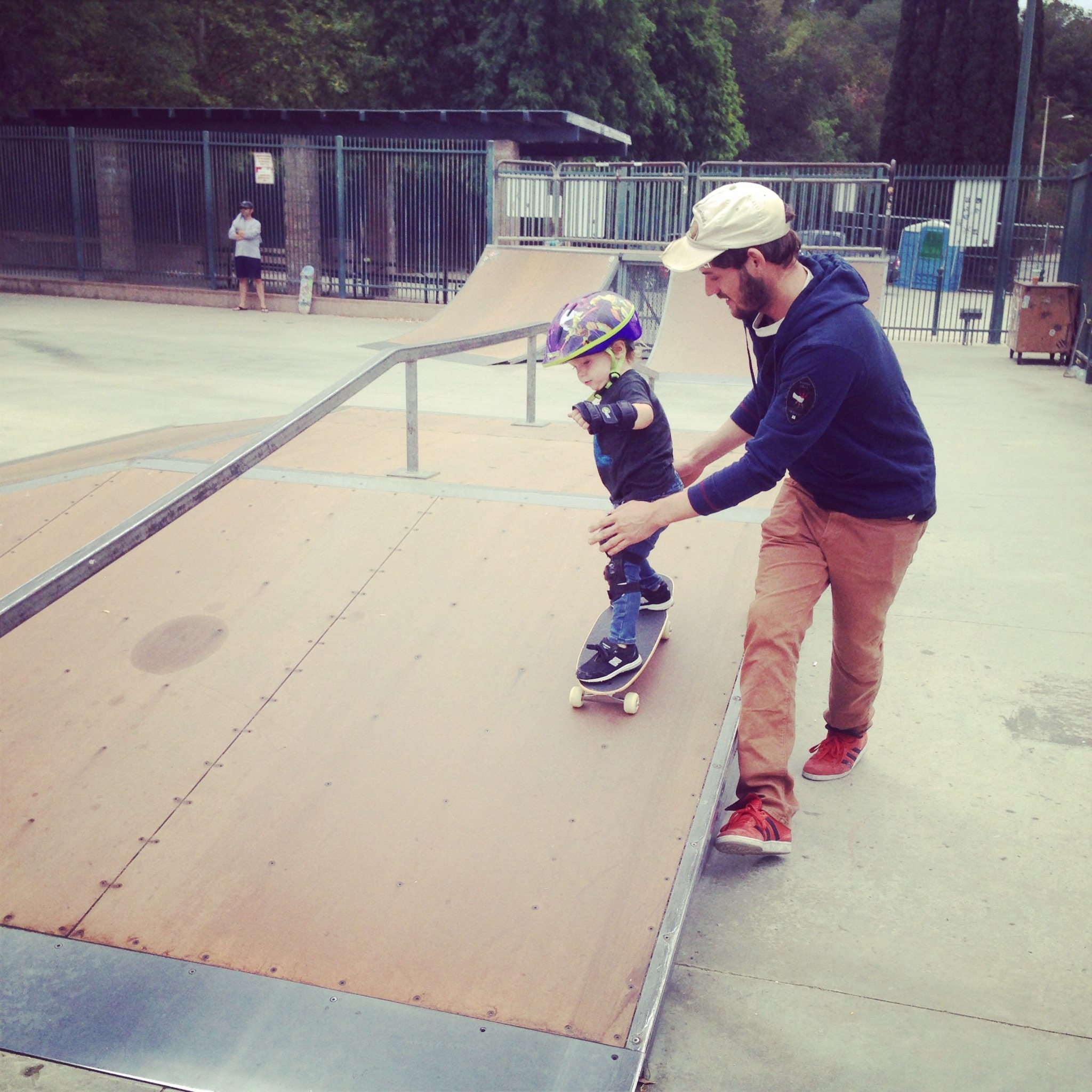 toddler on skateboard with dad