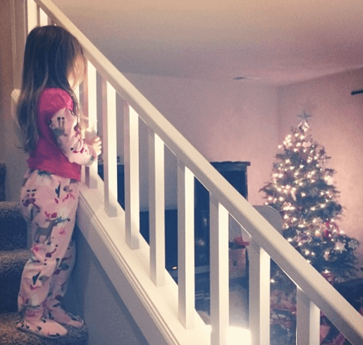 little girl looking at christmas tree