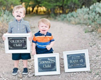 two little boys holding baby signs