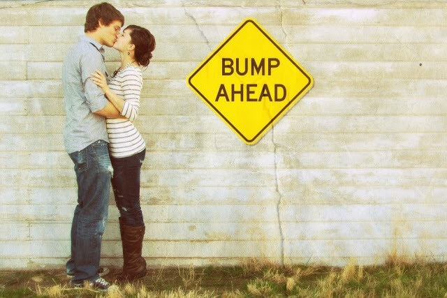 couple kissing in front of bump ahead sign