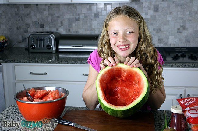 girl showing the inside of a carved out watermelon