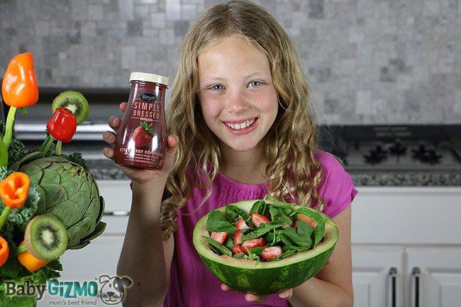 little girl holding strawberry dressing