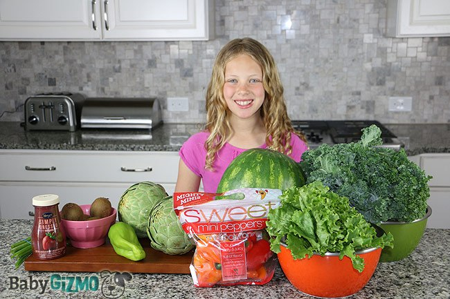 girl standing in front of counter produce