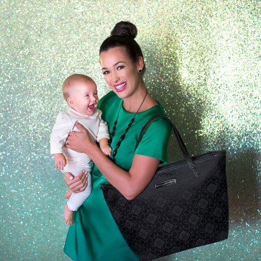 mom holding baby with black diaper bag