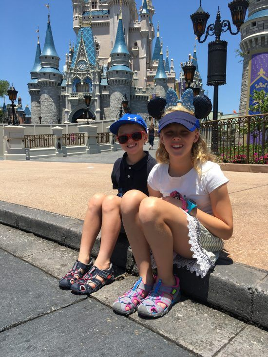 two kids sitting in front of Disney Castle