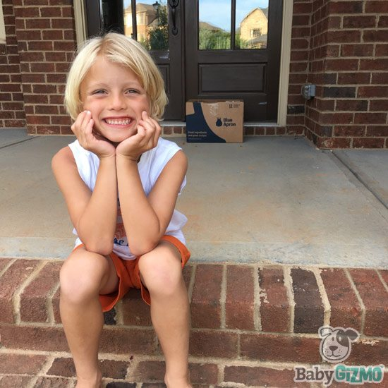 little boy sitting on porch and Blue Apron box in background