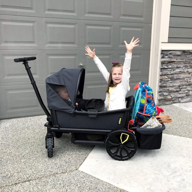 little girl with arms up in wagon