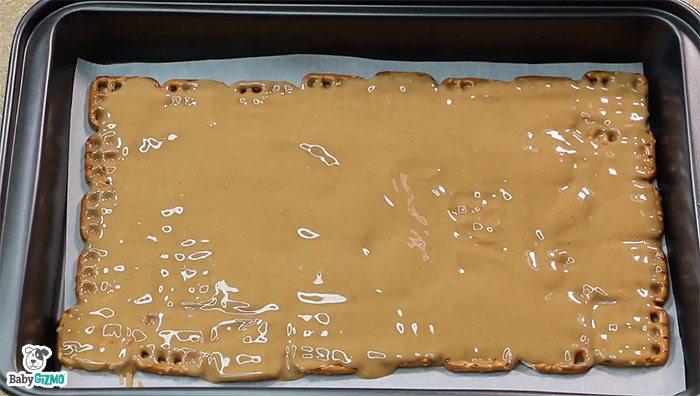 peanut butter on pretzels in baking pan