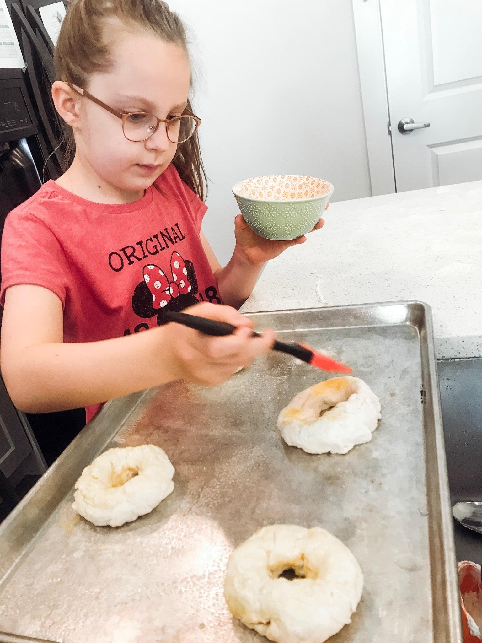 little girl brushing egg on bagels