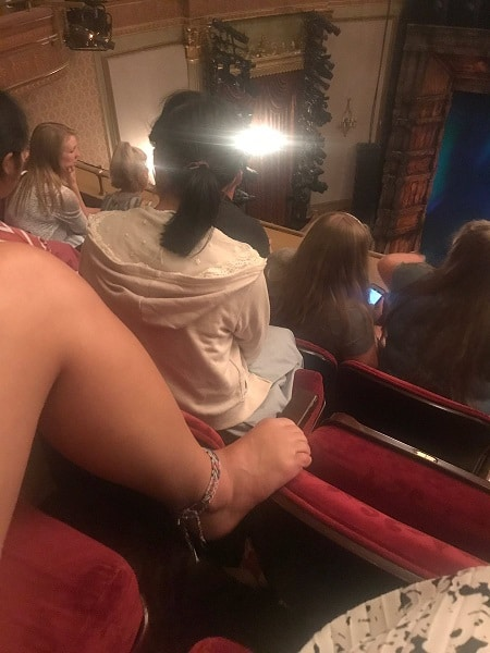 Bare feet on the back of a red velvet theater seat.