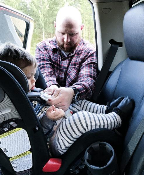 dad buckling child into car seat