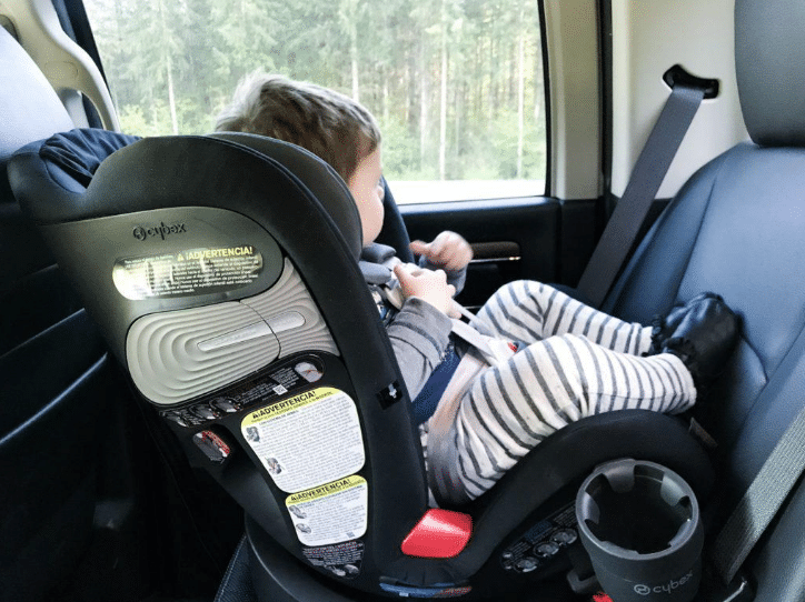 baby in car seat looking out window