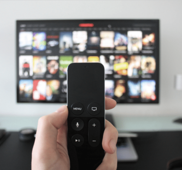 tv remote in hand blurred background with netflix on tv