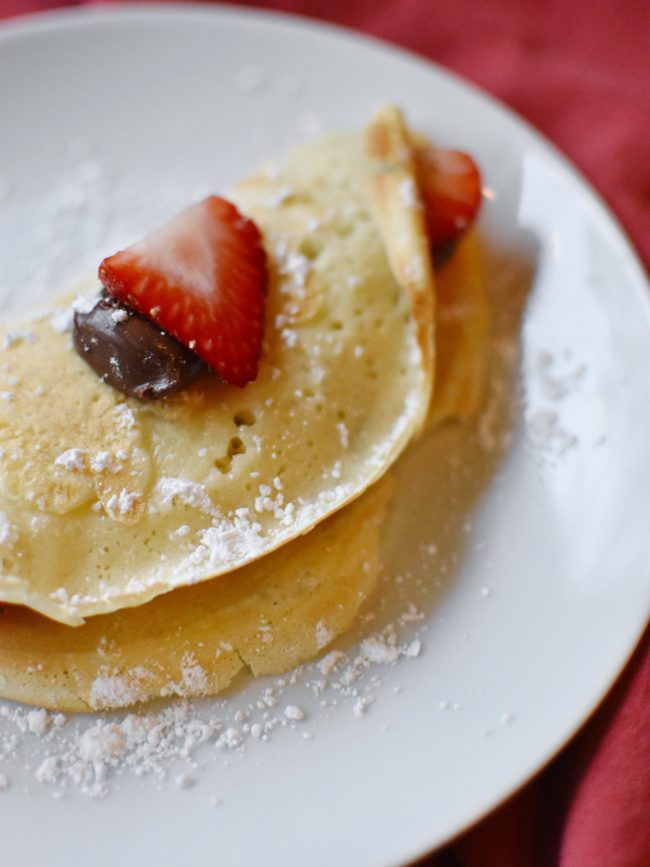crepes with strawberry and nutella on white plate