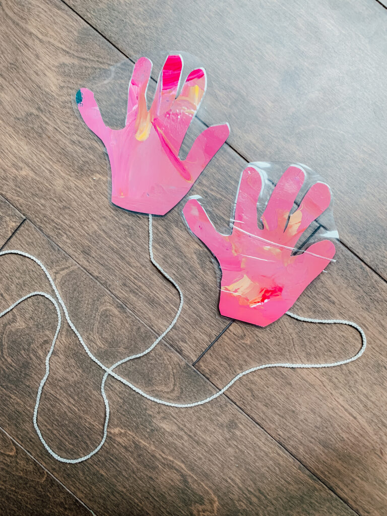 two hands of construction paper on a string
