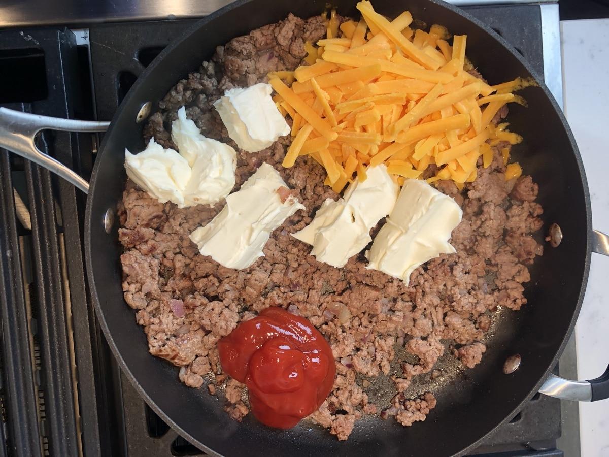 Cheeseburger ingredients in skillet