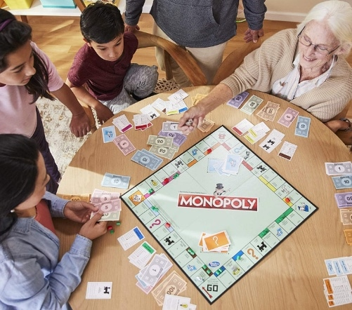 family playing monopoly around a table