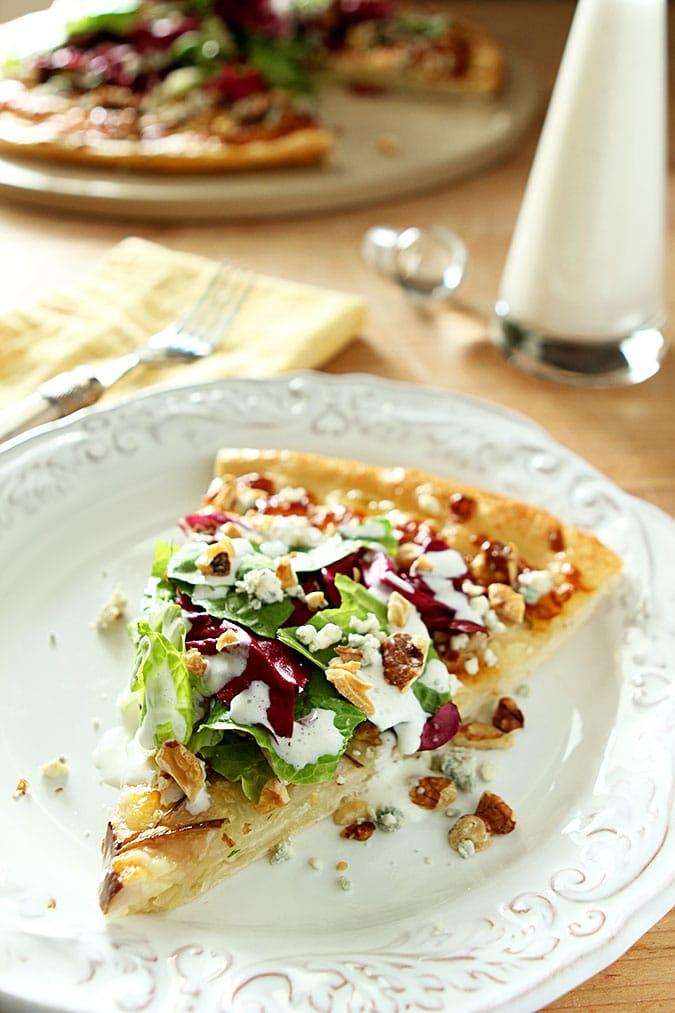 pear, gorgonzola and hazelnut pizza slice on white plate