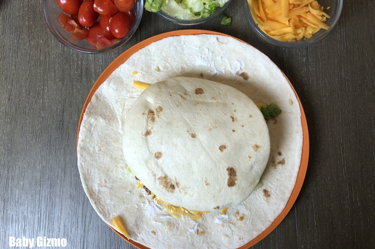 Tortilla with meat cheese on orange plate