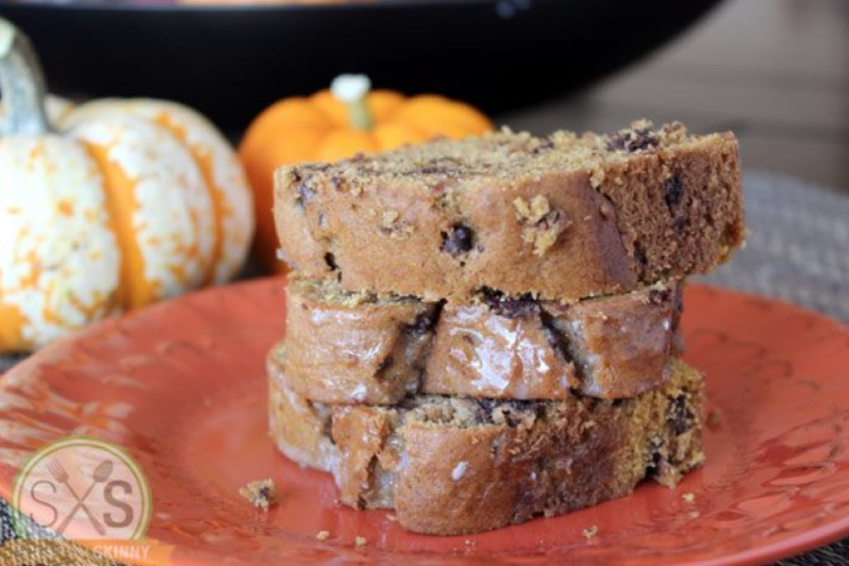 Three pieces of bread stacked next to pumpkins