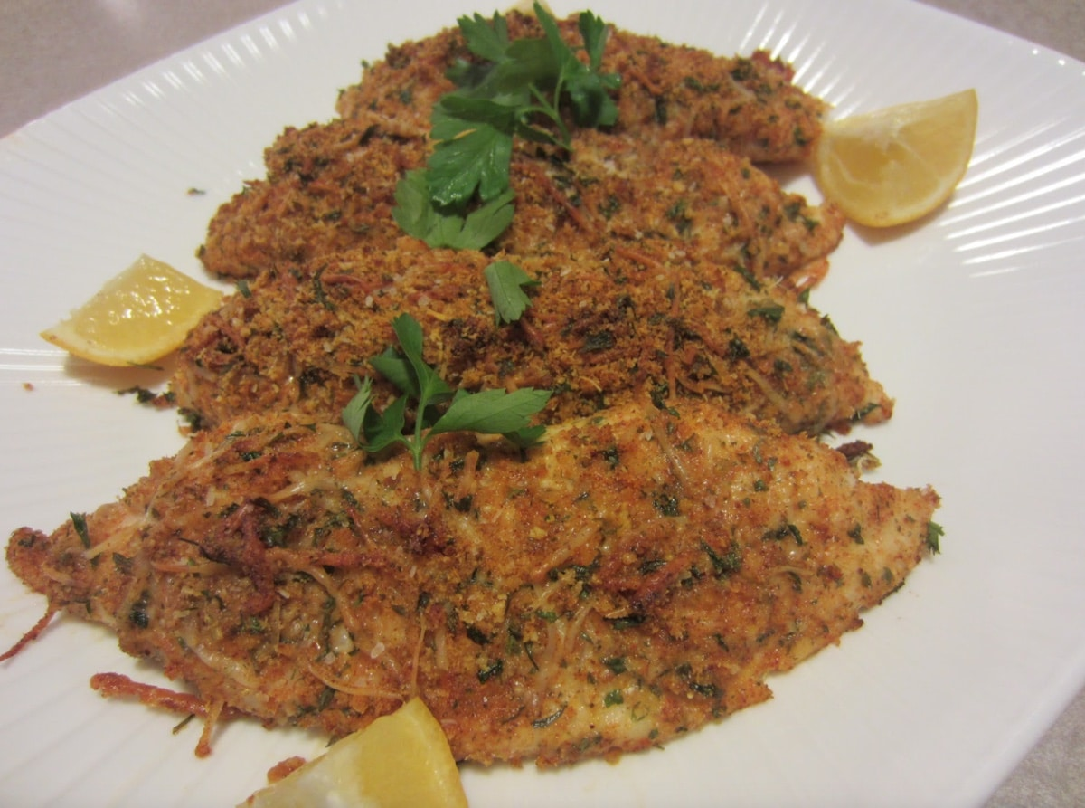 parmesan crusted tilapia on a white plate