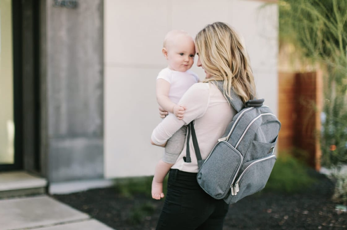 mom holding baby with grey backpack