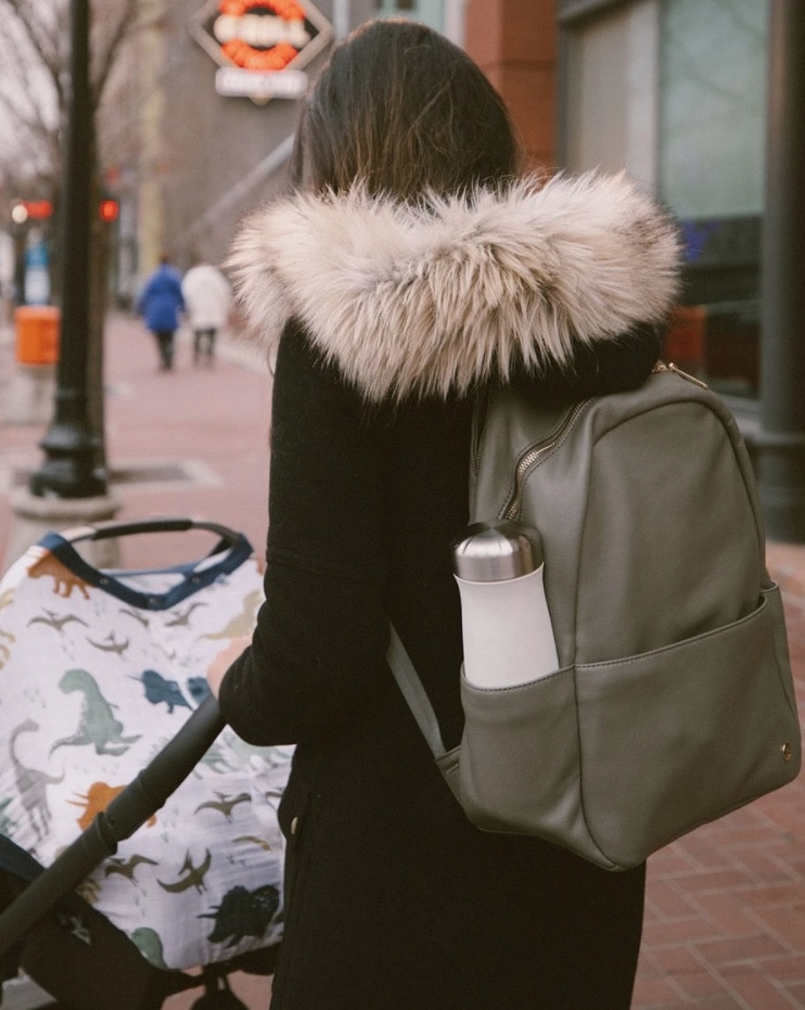 mom wearing diaper bag backpack pushing stroller