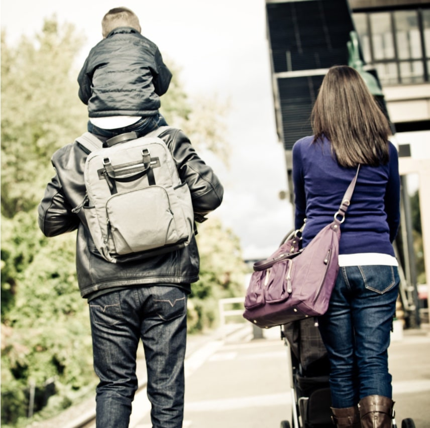 mom and dad and toddler walking with bags