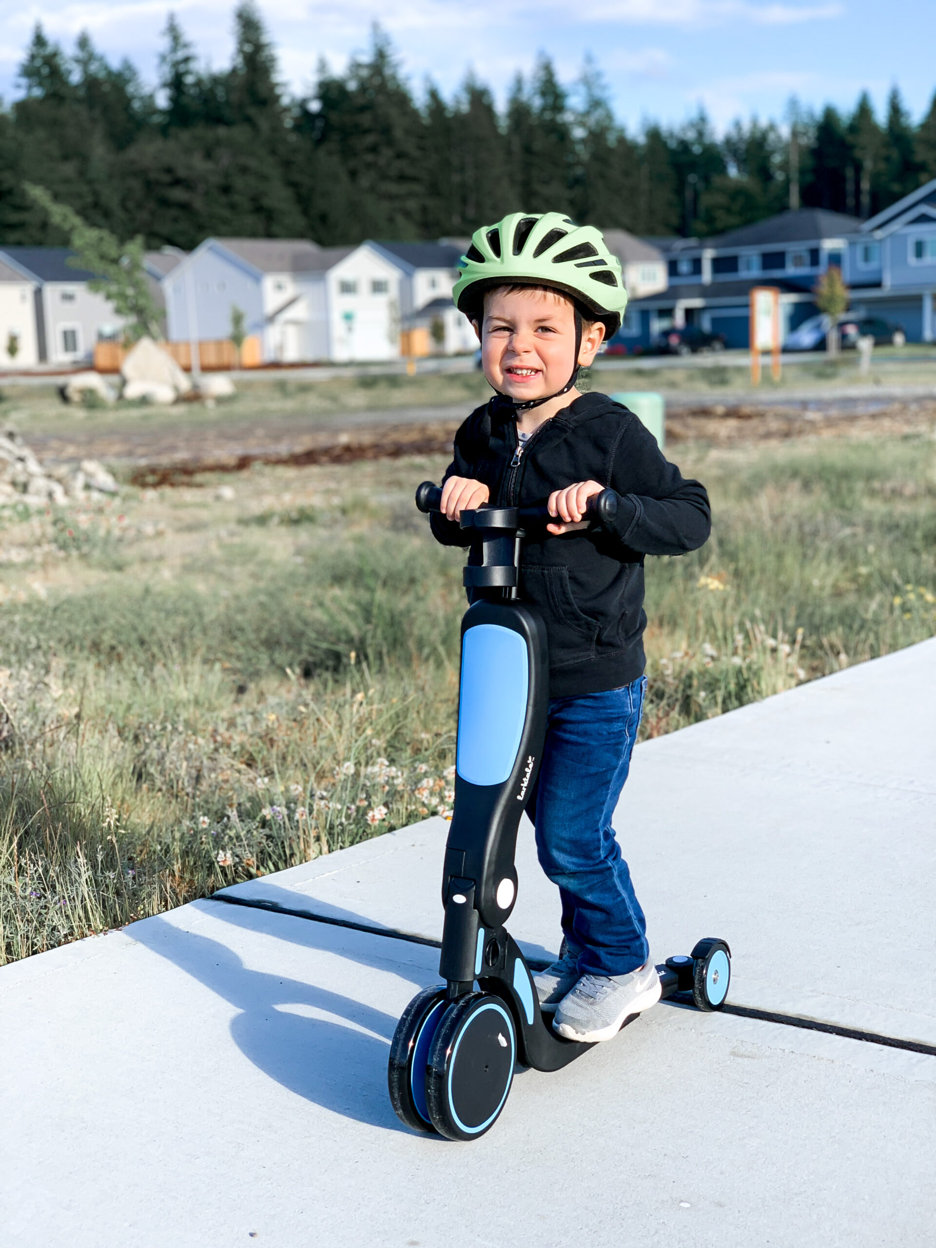 little boy on blue and black scooter