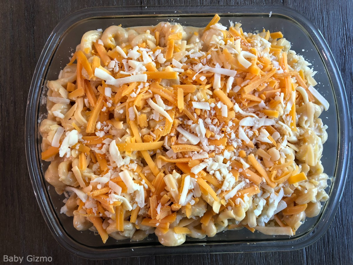 Homemade mac and cheese in glass dish with shredded cheese on top.