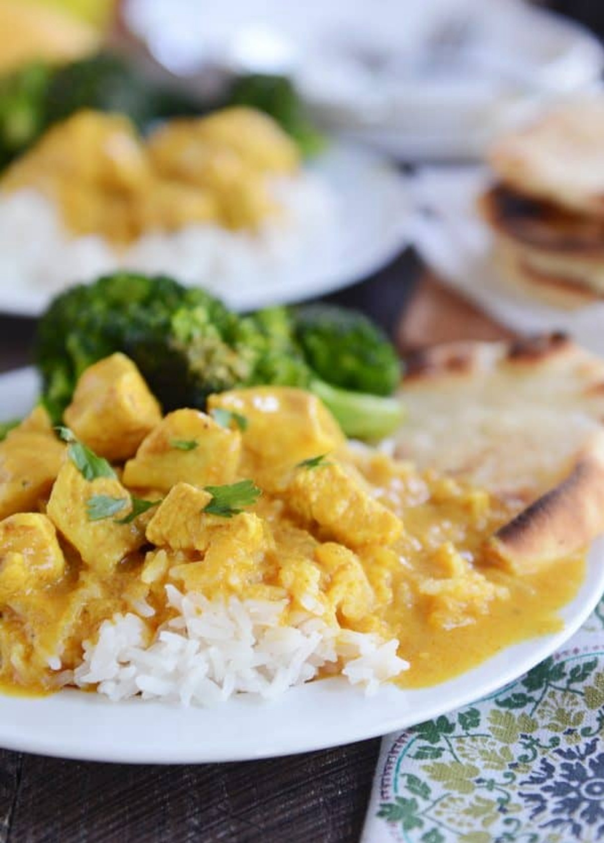 Mango Chicken Red Curry dish on a white plate with broccoli side
