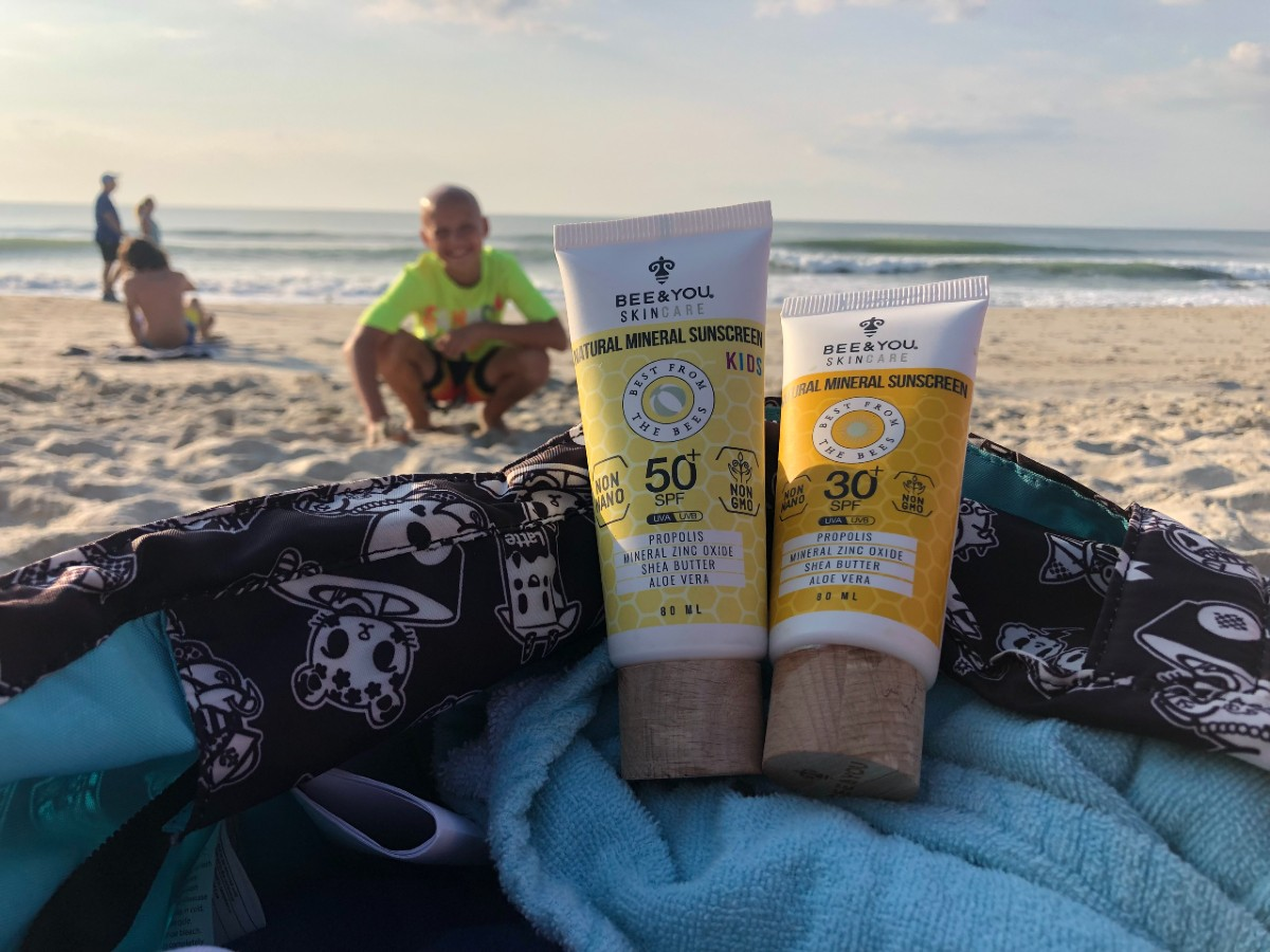 two bottles of sunscreen with boy in the background