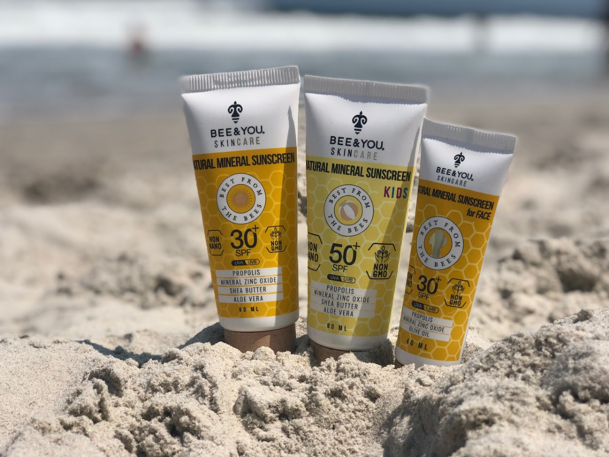 three bottles of natural sunscreen in the sand