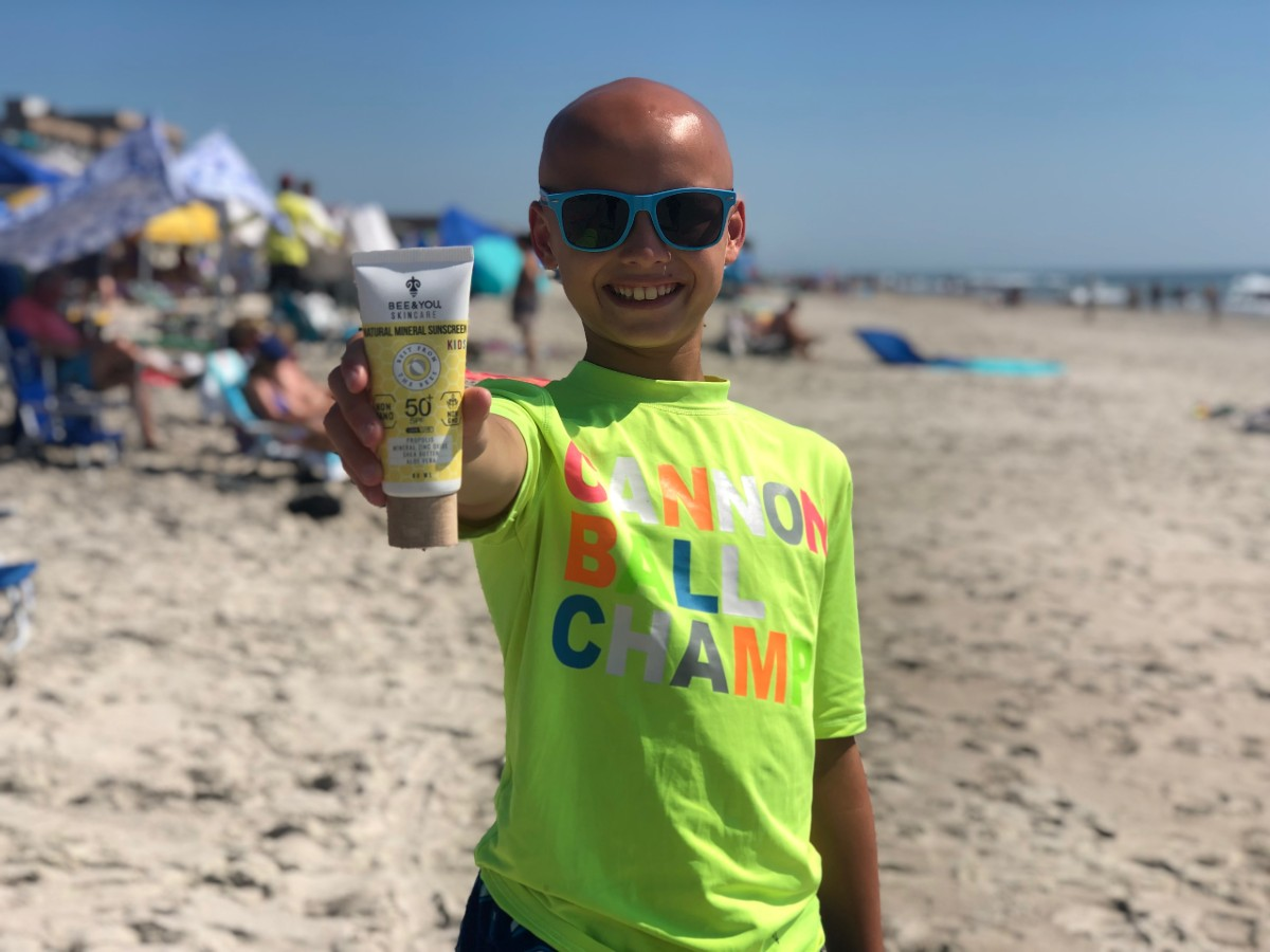 bald boy holding out sunscreen in hand on the beach