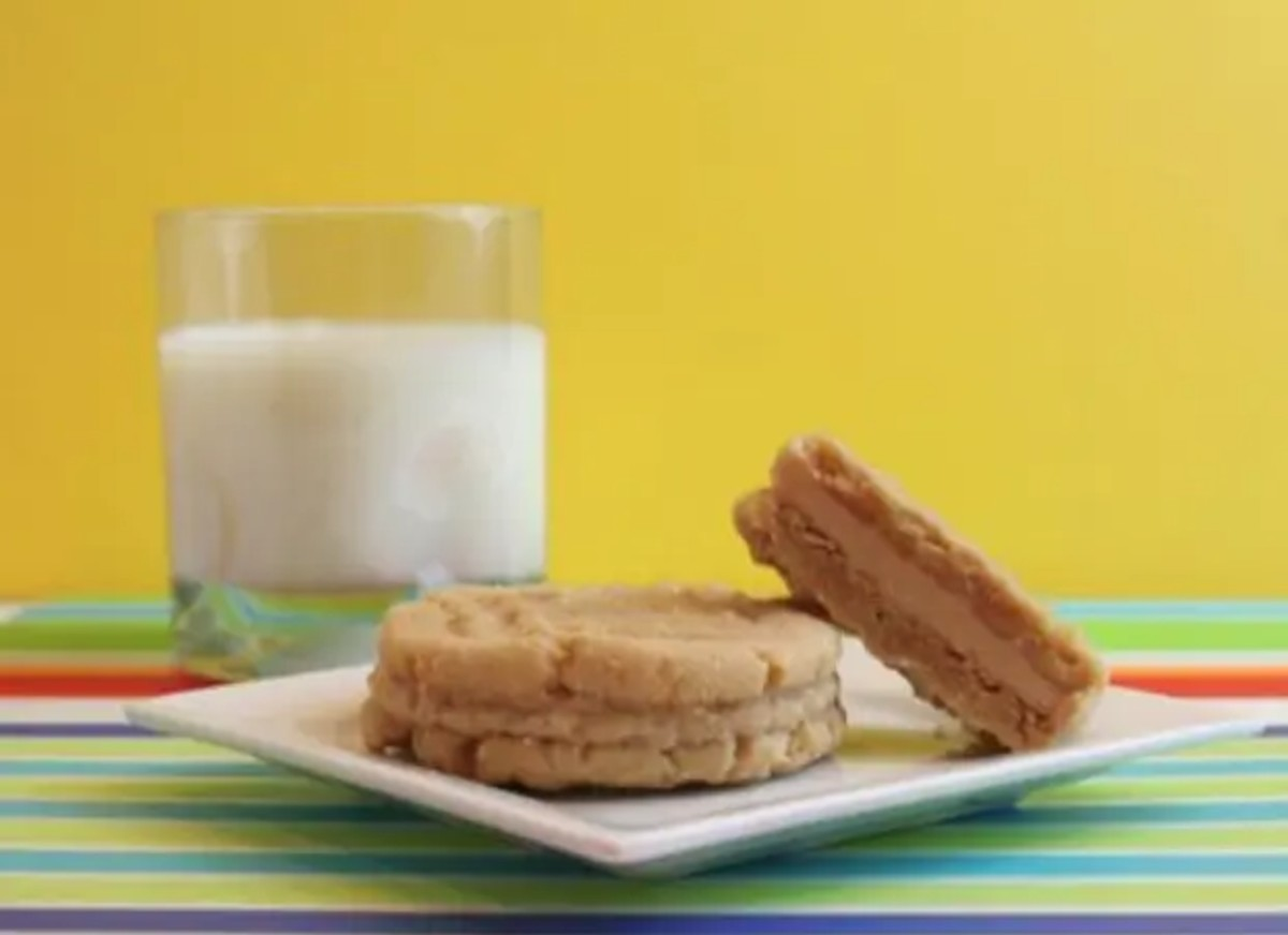 2 homemade nutter butter cookies with milk in the background