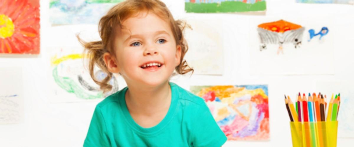 preschool girl with art behind her