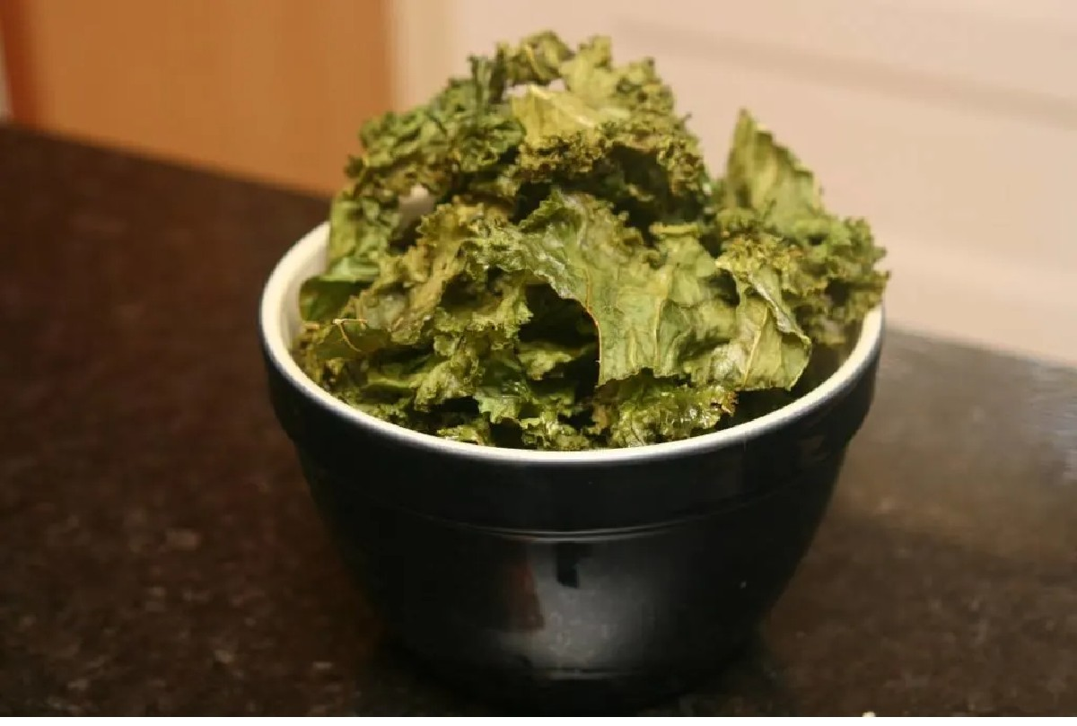 Lots of kale chips in a black bowl
