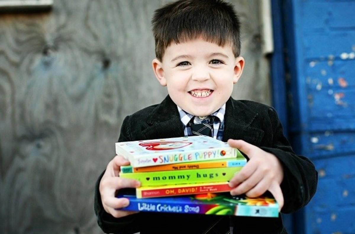 little boy holding stacks of books