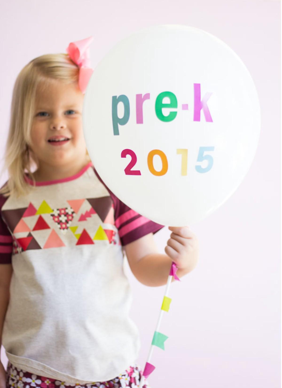 little girl holding balloon