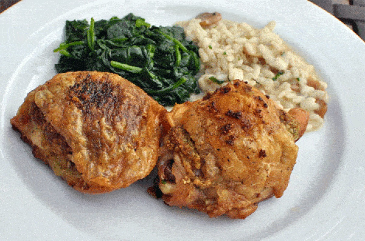 pesto roasted chicken thighs on a white plate with rice