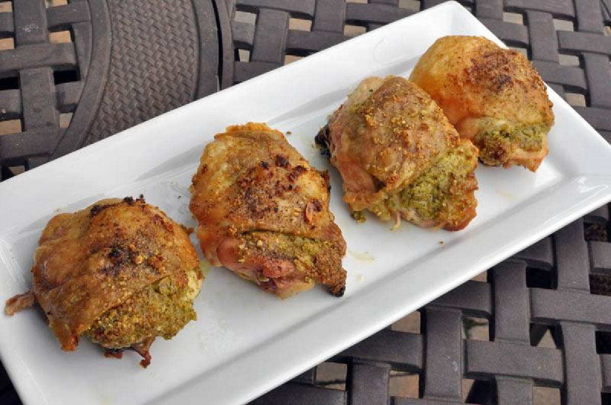 pesto roasted chicken thighs on a white plate