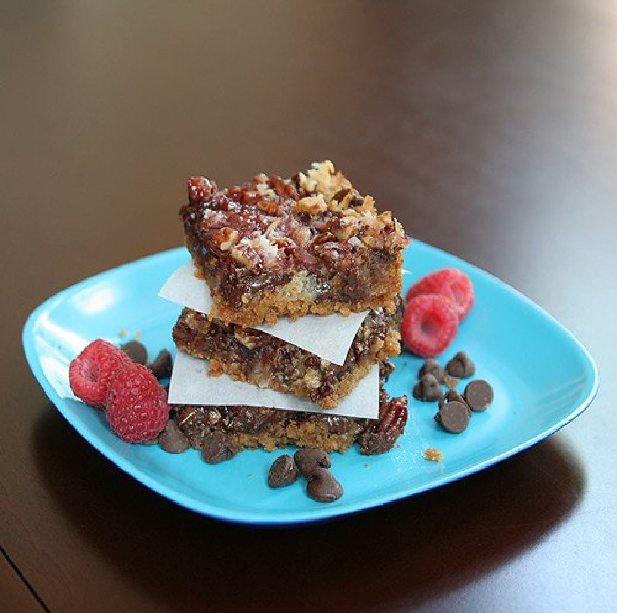 3 raspberry magic bars stacked on top of each other on a blue plate with raspberries and chocolate chips on the side