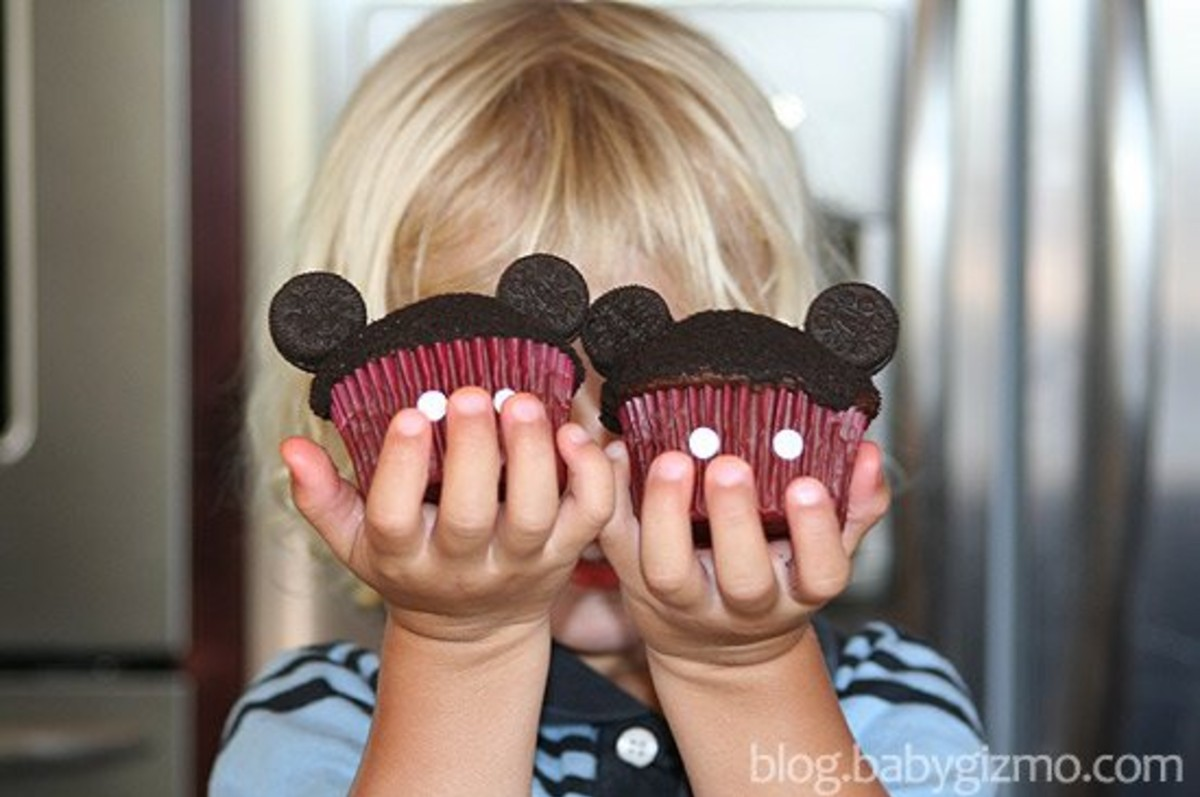 a kid holding two mickey mouse cupcakes in each hand